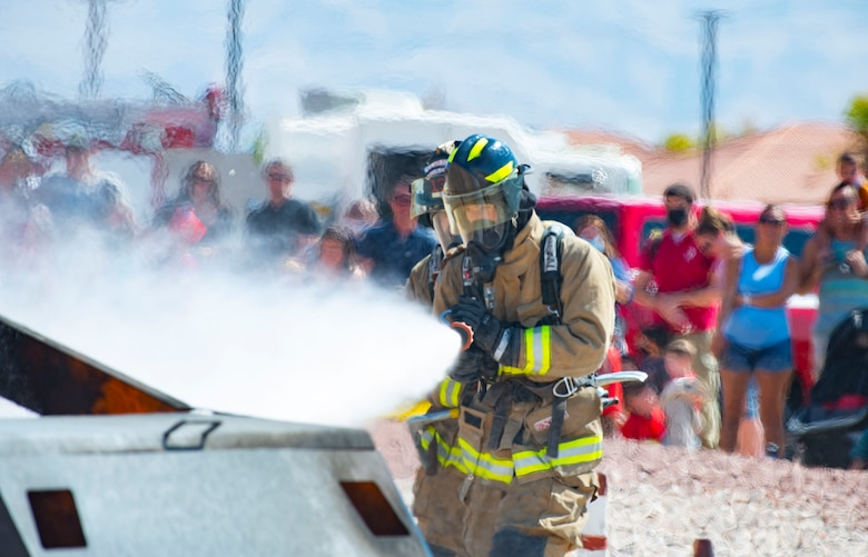 Firefighters extinguish car fire during demonstration.