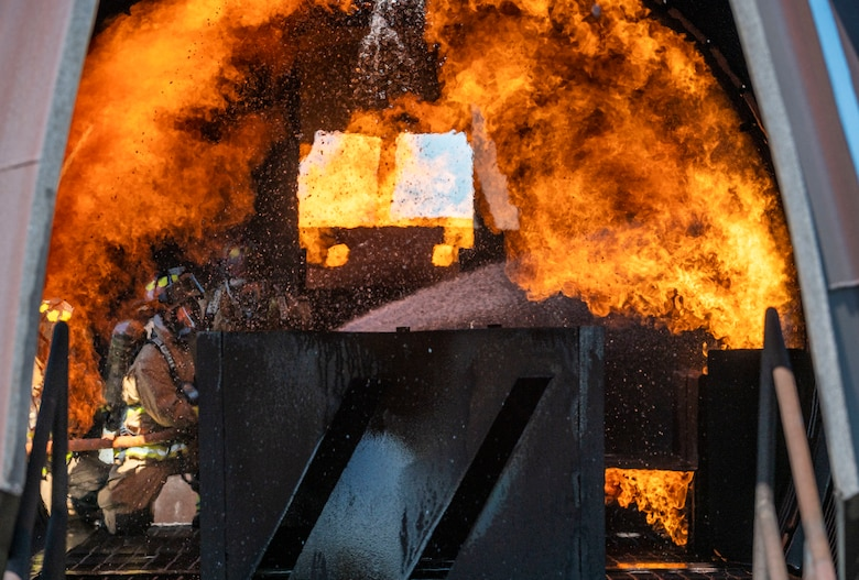 Firefighters from the 436th Civil Engineer Squadron and 177th Civil Engineer Squadron extinguish flames inside an aircraft live-fire trainer during joint training at Dover Air Force Base, Delaware, Sept. 22, 2020. Total Force and civilian fire companies in the surrounding community often partner with Dover AFB to complete annual training requirements. (U.S. Air Force photo by Senior Airman Christopher Quail)