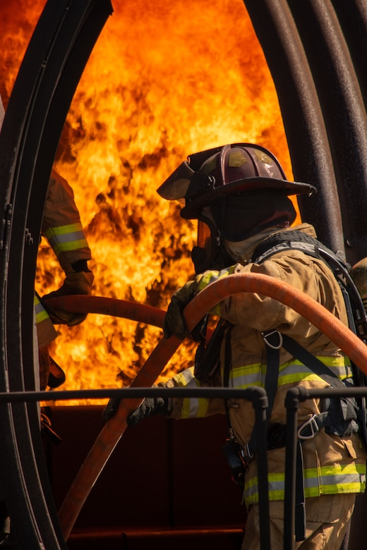A U.S. Air Force firefighter pulls a fire hose into an aircraft fire trainer during a training exercise at Dover Air Force Base, Delaware, Sept. 22, 2020. Temperatures inside the aircraft fire trainer can reach up to 1,500 degrees Fahrenheit. (U.S. Air Force photo by Airman Brandan Hollis)