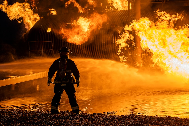 A firefighter from the 436th Civil Engineer Squadron monitors a live-fire-burn exercise at night Sept. 28, 2020, on Dover Air Force Base, Delaware. Total Force and civilian fire companies in the surrounding community often partner with Dover AFB to complete annual training requirements. (U.S. Air Force photo by Senior Airman Christopher Quail)