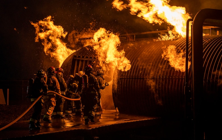 Firefighters from the 436th Civil Engineer Squadron and Magnolia Volunteer Fire Company Station 55, from Delaware, spray down an aircraft-fire trainer during a  live-fire-burn exercise at night Sept. 28, 2020, on Dover Air Force Base, Delaware. Total Force and civilian fire companies in the surrounding community often partner with Dover AFB to complete annual training requirements.. (U.S. Air Force photo by Senior Airman Christopher Quail)