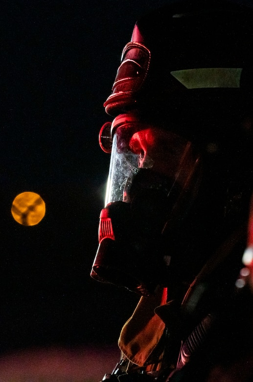 A firefighter from the 436th Civil Engineer Squadron watches a live-fire-burn exercise at night Sept. 28, 2020, on Dover Air Force Base, Delaware. Total Force and civilian fire companies in the surrounding community often partner with Dover AFB to complete annual training requirements. (U.S. Air Force photo by Senior Airman Christopher Quail)