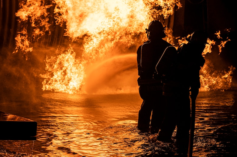 Firefighters from the 436th Civil Engineer Squadron and Magnolia Volunteer Fire Company Station 55, from Delaware, spray down an aircraft fire trainer during a live-fire-burn exercise at night Sept. 28, 2020, on Dover Air Force Base, Delaware. Temperatures inside the aircraft-fire trainer can reach up to 1,500 degrees Fahrenheit. (U.S. Air Force photo by Senior Airman Christopher Quail)