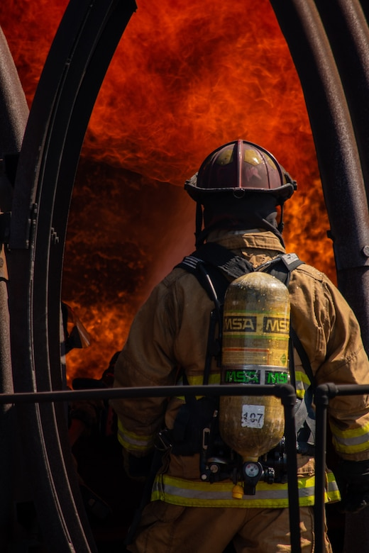 A U.S. Air Force firefighter enters an aircraft fire trainer during an exercise at Dover Air Force Base, Delaware, Sept. 22, 2020. Temperatures inside the aircraft fire trainer can reach up to 1,500 degrees Fahrenheit. (U.S. Air Force photo by Airman Brandan Hollis)