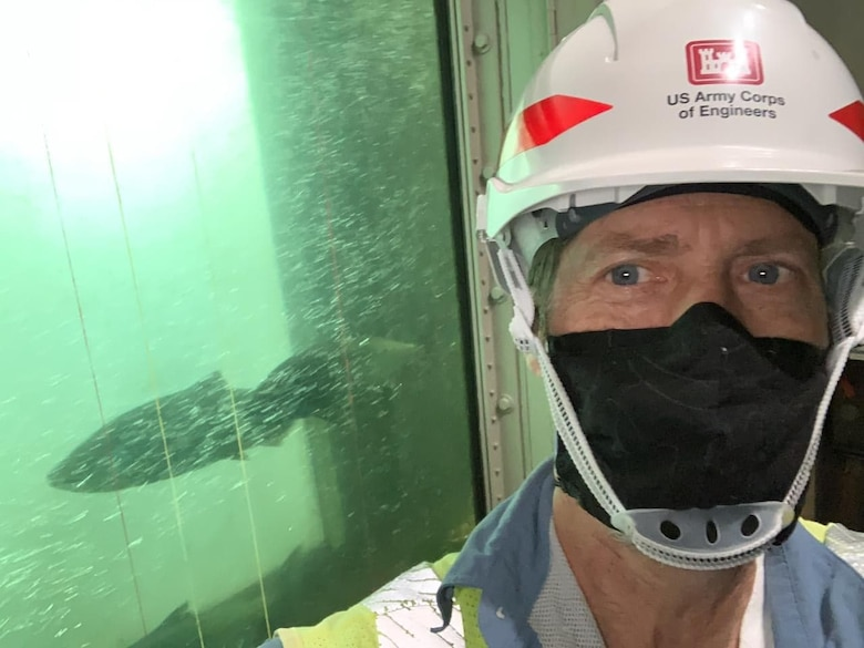 Jim Day, fisheries biological technician at The Dalles Lock and Dam, snaps a selfie in front of the East fish counting station window. Fish are counted as they swim through the fish ladders at the dam.
