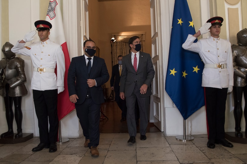 Two Maltese soldiers salute as men leave room.