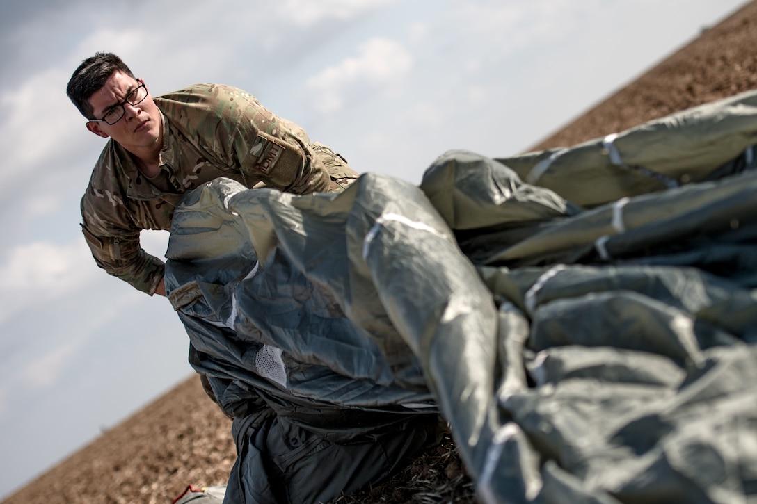 Photo of Airman gathering a deflated parachute