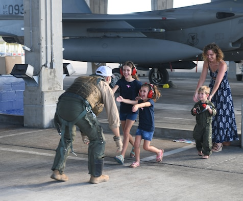 U.S. Air Force Maj. Jonathan Taylor, 44th Fighter Squadron assistant director of operations, is welcomed back from a deployment by his family Oct. 3, 2020, at Kadena Air Base, Japan. While deployed to the U.S. Central Command area of operations, Airmen conducted more than 1,000 sorties and 5,300 combat hours, which drove 13 phase inspections in six months. They'll now share the skills they learned in combat with Team Kadena, joint partners and allies to ensure a free and open Indo-Pacific. (U.S. Air Force photo by Tech. Sgt. Benjamin Sutton)