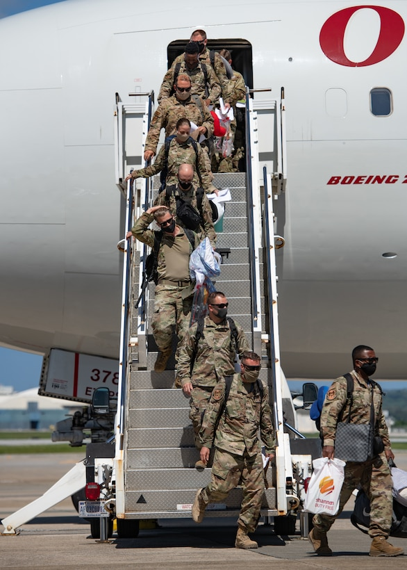 Airmen from the 18th Wing disembark an aircraft upon their return from a deployment to U.S. Central Command Oct. 6, 2020, at Kadena Air Base, Japan. More than 300 Airmen assigned to the 18th Operations and Maintenance Groups as well as pilots and aircraft assigned to the 44th Fighter Squadron deployed to the CENTCOM theater to defend U.S. and partner nation interests. During their deployment, Airmen conducted more than 1,000 sorties and 5,300 combat hours, which drove 13 phase inspections in six months. They'll share the skills they learned in combat with Team Kadena, joint partners and allies to ensure a free and open Indo-Pacific. (U.S. Air Force photo by Staff Sgt. Peter Reft)