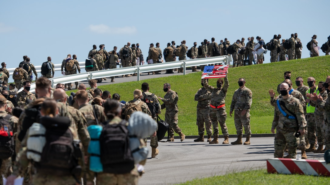 Members of the 18th Wing walk toward the air terminal at Kadena Air Base, Japan, after returning from a deployment to U.S. Central Command Oct. 6, 2020. More than 300 Airmen assigned to the 18th Operations and Maintenance Groups as well as pilots and aircraft assigned to the 44th Fighter Squadron deployed to the CENTCOM theater to defend U.S. and partner nation interests. During their deployment, Airmen conducted more than 1,000 sorties and 5,300 combat hours, which drove 13 phase inspections in six months. They'll share the skills they learned in combat with Team Kadena, joint partners and allies to ensure a free and open Indo-Pacific. (U.S. Air Force photo by Staff Sgt. Peter Reft)