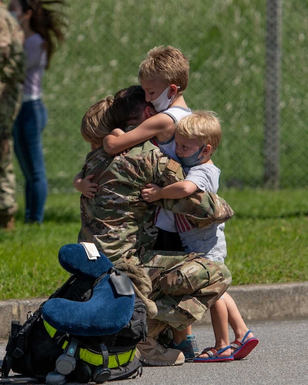 A U.S. Air Force Airman embraces his children upon returning from a deployment to U.S. Central Command Oct. 6, 2020, at Kadena Air Base, Japan. Airmen from the 18th Operations and Maintenance Groups deployed to the CENTCOM area of responsibility in support of ongoing operations to maintain air superiority, defend forces on the ground, enhance regional partnerships, and demonstrate a continued commitment to regional security and stability. (U.S. Air Force photo by Staff Sgt. Peter Reft)
