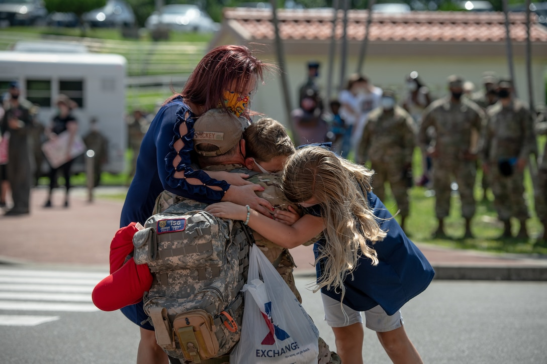 U.S. Air Force Master Sgt. Jereme Tockey, 18th Aircraft Maintenance Squadron first sergeant, embraces his family after returning from a deployment to U.S. Central Command Oct. 6, 2020, at Kadena Air Base, Japan. While deployed to the CENTCOM area of responsibility, Airmen conducted more than 1,000 sorties and 5,300 combat hours, which drove 13 phase inspections in six months. They'll share the skills they learned in combat with Team Kadena, joint partners and allies to ensure a free and open Indo-Pacific. (U.S. Air Force photo by Staff Sgt. Peter Reft)