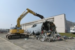 A track excavator tears through a C-130 Hercules along the flight line at Hanscom Air Force Base in Massachusetts. The transport aircraft had been used as a base trainer for decades, until it was removed in September through a DLA Disposition Services Demilitarization as Condition of Sale contract.