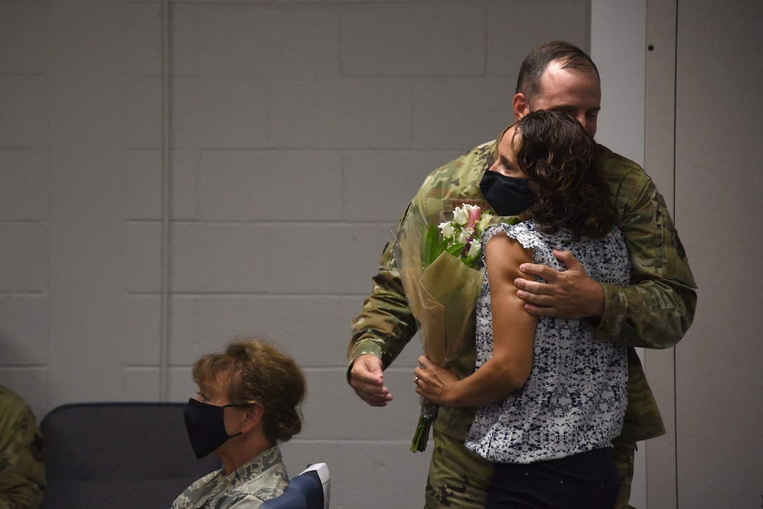 U.S. Air Force Lt. Col. Michael Kosderka, new 142nd Maintenance Group commander, hugs his wife during a change of command ceremony at Portland Air National Guard Base, Portland, Ore., Oct. 1, 2020. Kosderka assumed command from Col. William Kopp, who took over as the 142nd Wing Vice Commander. (U.S. Air National Guard Photo by Senior Airman Valerie R. Seelye)