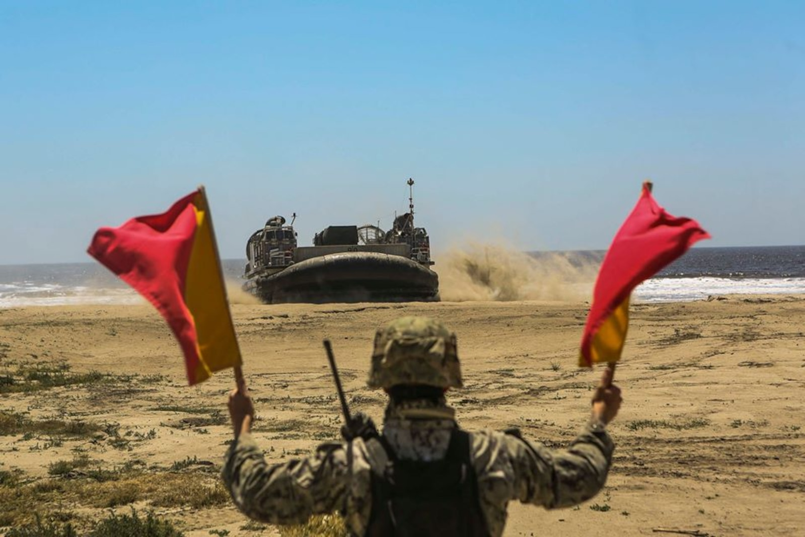 Landing Support Specialist from LS Co, 1st TSB direct an LCAC conducting a landing aboard Red Beach, Camp Pendleton on 4 May 2020.