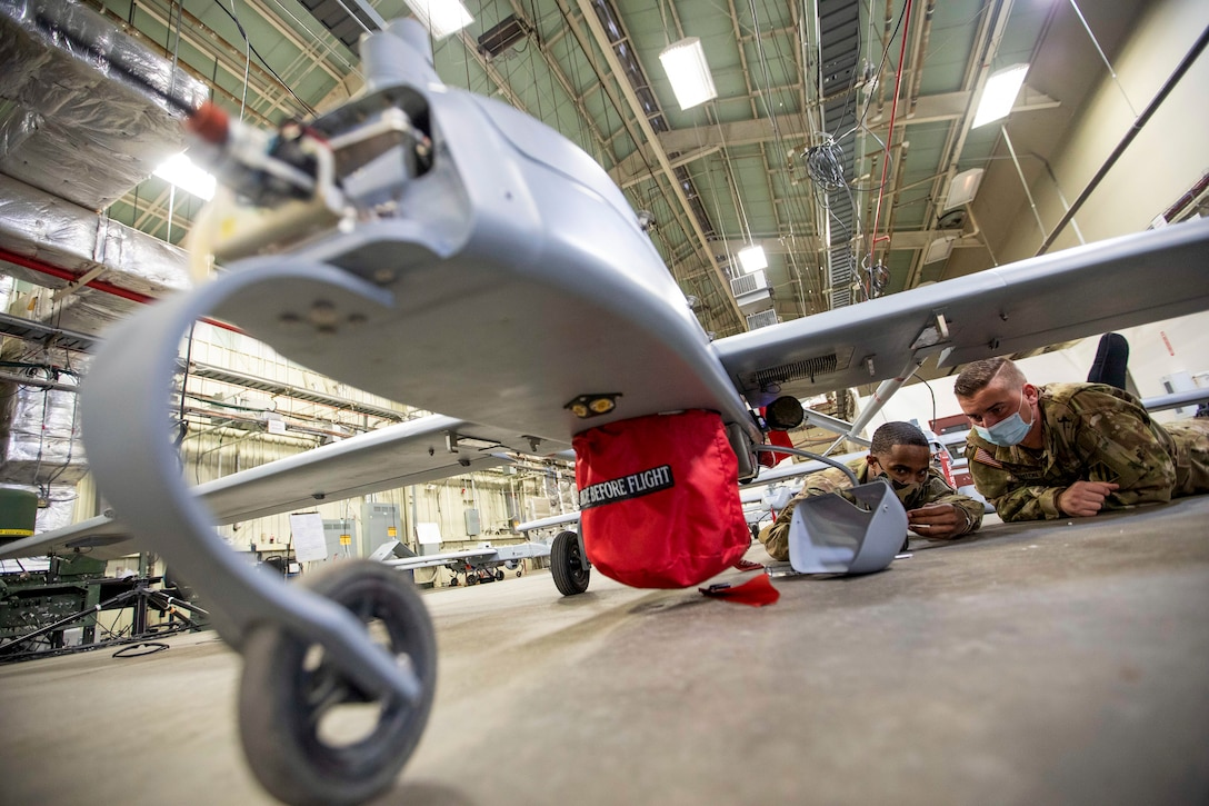 Two soldiers lie prone while working on an unmanned aircraft system in a hangar-type facility.
