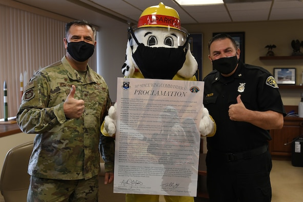Col. Anthony Mastalir, 30th Space Wing commander, and Mark Farias, 30th Civil Engineer Squadron fire chief, and Sparky the Fire Dog pose with the signed 2020 Fire Proclamation Oct. 5, 2020, at Vandenberg Air Force Base, Calif.
