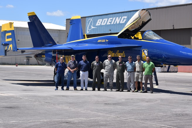 Nine people stand in front of a blue fighter jet with yellow trim.