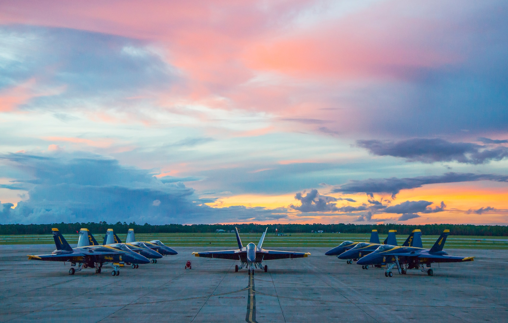 Seven blue fighter jets are parked in front of a dramatic evening sky