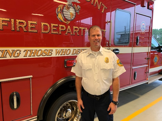 Assistant fire chief stands in front of fire truck