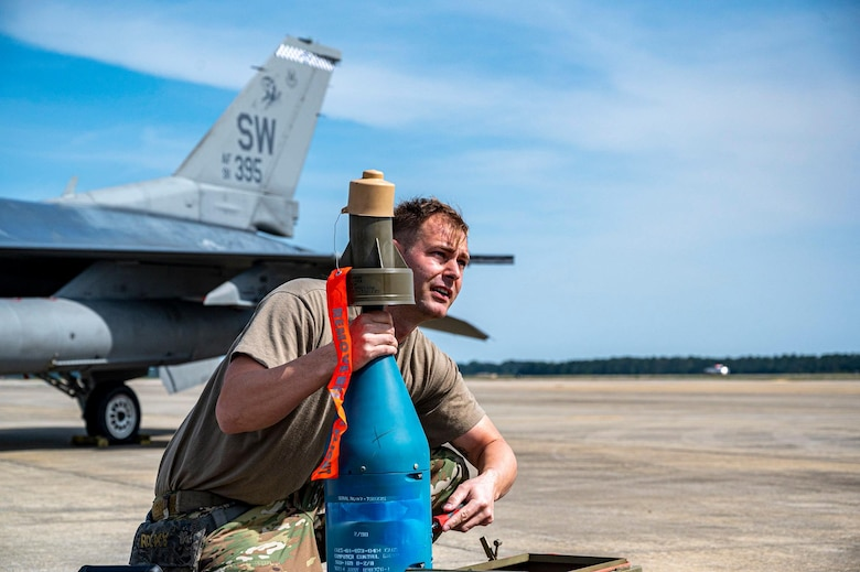 An Airman holds a munition on the flightline.
