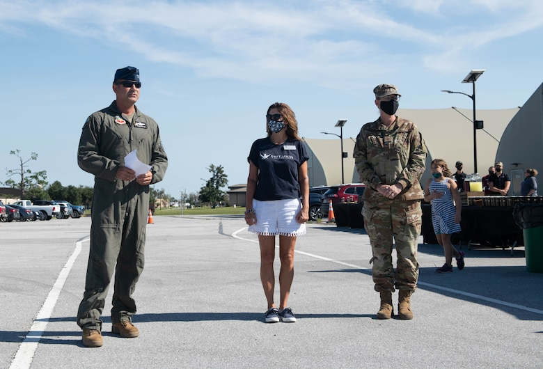 Col. Greg Moseley delivers a speech alongside Lisa Lowry, and Chief Master Sgt. Katherine Grabham