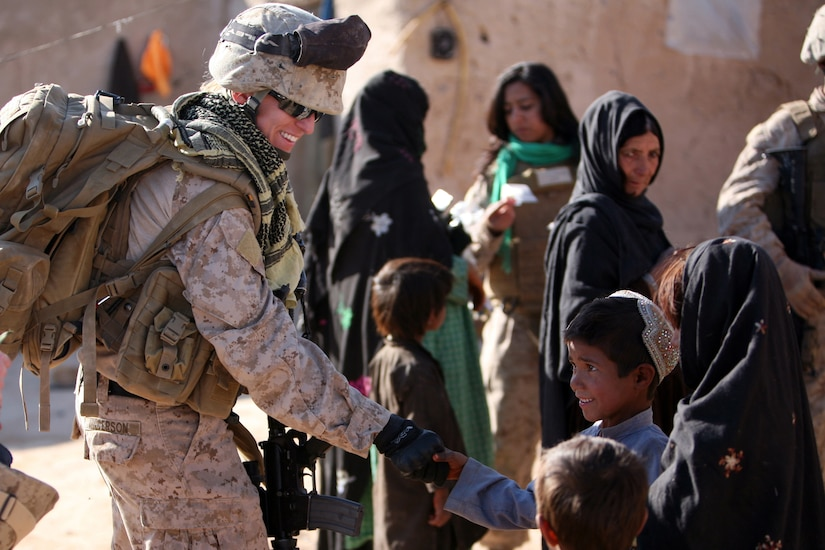 A woman in a military uniform shakes hands with a young boy. Other women and children are milling about in the background.