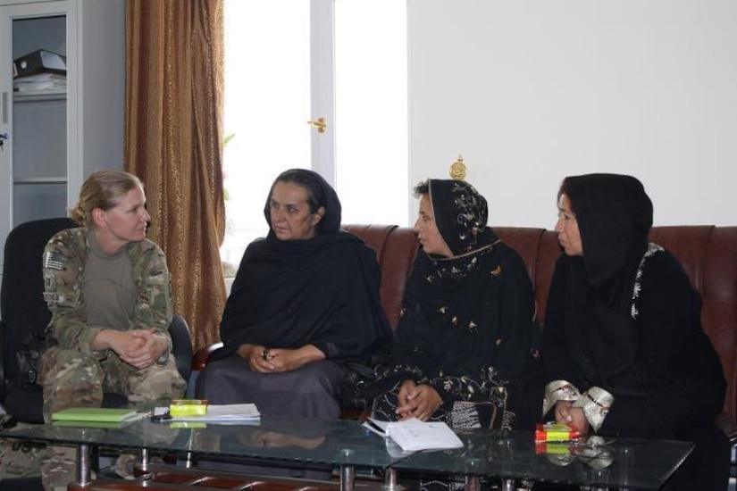 Three women in black robes sit on a couch and talk to a woman in a military uniform who is sitting on a chair.