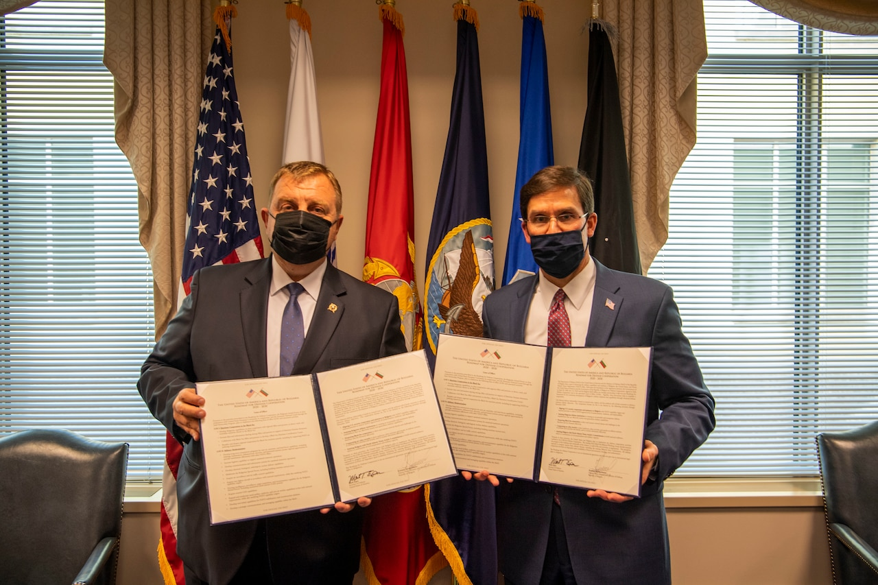 Two men hold two government documents as they pose for a photo.