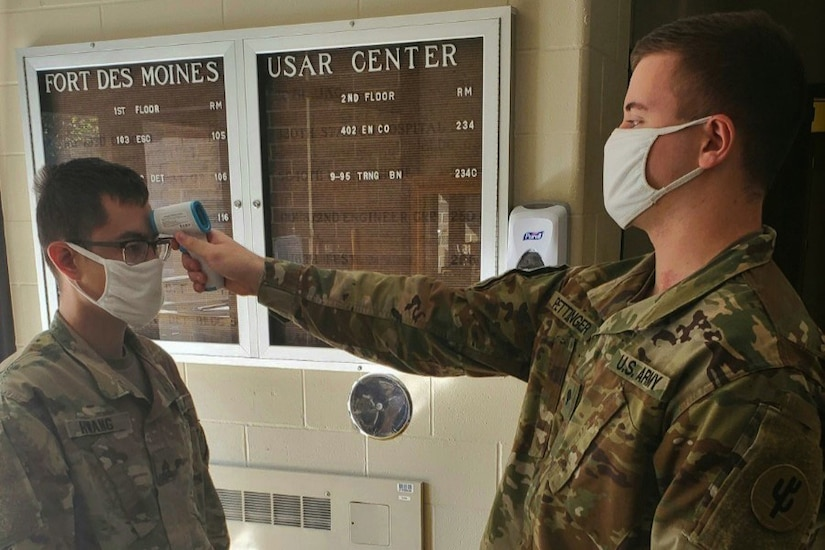 A soldier wearing a face mask takes the temperature of another soldier wearing a face mask.