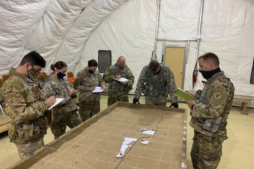 Soldiers wearing face masks having a meeting.