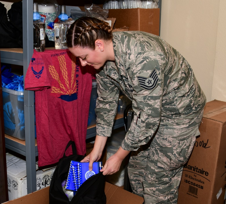 A photo of an Airman packing a bag with pads of paper for an event.