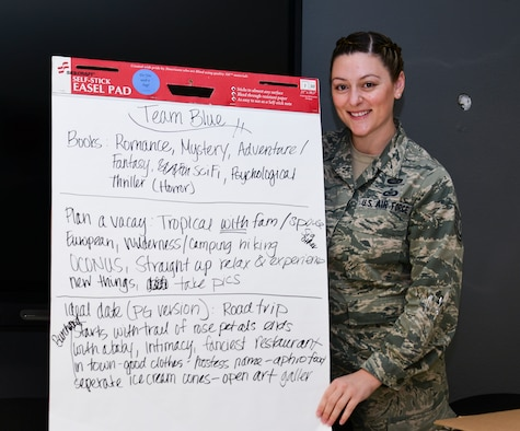 """A photo of an Airman posing with a sign with the prominent """"True Color"""" being blue."""