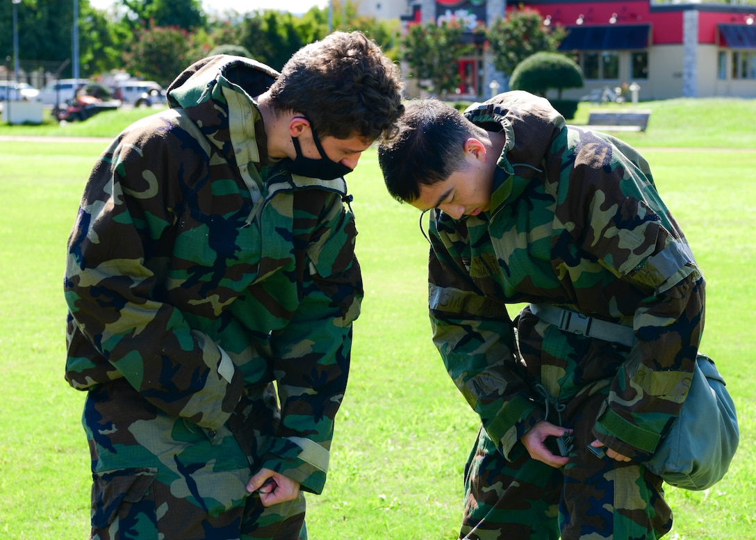 Airman 1st Class Adam Vittiello, 374th Force Support Squadron food services journeyman, left, ensures his wingman, Senior Airman Yinxiao Wu, 374th FSS fitness journeyman, dons his Mission Oriented Protective Posture gear accurately during the squadron's war fighting training day.
