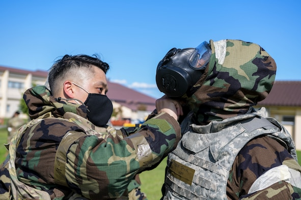 Capt. Jesse Salgado, 374th Force Support Squadron operations officer, left, fastens the hood over the mask for Tech. Sergeant Christopher Smith, 374th Force Support Squadron postmaster during the squadron's war fighting training day.
