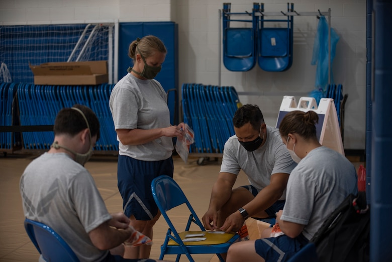 Master Sgt. Matthew Stickley, Maj. Lori Wyatt, Master Sgt. Jordan Killebrew, and 1st Lt. Hannah Staubs prepare COVID-19 nasal swab testing kits at the West Virginia University Student Recreation Center, Morgantown, W. Va., Sept. 30, 2020. The Airmen are assigned to West Virginia National Guard's task force medical team, which has been assisting county health departments throughout the state during the pandemic.