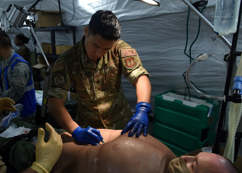 Maj. Christopher Ng, assigned to the 48th Surgical Services Squadron, performs a simulated surgery during Mission Assurance Exercise 20-20 at Royal Air Force Feltwell, England, Sept. 29, 2020. During the exercise, medical personnel received unique training and challenged their proficiency, practicing medical skills and procedures while treating simulated injuries in a forward operating location. (U.S. Air Force photo by Airman 1st Class Rhonda Smith)