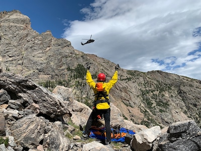A Colorado Army National Guard UH-60 Black Hawk helicopter from the Army Aviation Support Facility, Buckley Air Force Base, Aurora, Colorado, approaches a member of the Alpine Rescue Team and an injured climber in Rocky Mountain National Park Aug. 30, 2019. The Colorado Hoist Rescue Team provides hoist extraction capability throughout Colorado by incorporating civilian alpine rescue personnel and military helicopter capabilities.