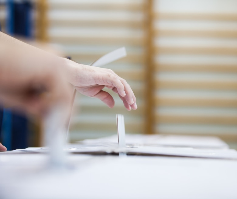 Hand is putting a ballot into a voting box.