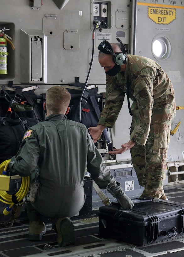 Tech. Sgt. Nickolaus Burns, 445th Aeromedical Evacuation Squadron flight instructor, shows a U.S. Air Force School of Aerospace Medicine student how to properly configure the medical equipment on a 445th Airlift Wing C-17 Globemaster III in preparation for an aeromedical evacuation training flight Sept. 14, 2020. Burns was one of four Reserve Citizen Airmen who augmented active duty cadre at the schoolhouse in September.