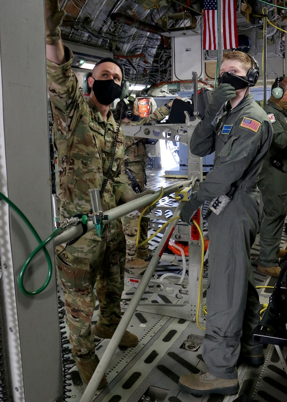 Tech. Sgt. Nickolaus Burns (left), 445th Aeromedical Evacuation Squadron flight instructor, shows a U.S. Air Force School of Aerospace Medicine student how to properly configure the medical equipment on a 445th Airlift Wing C-17 Globemaster III in preparation for an aeromedical evacuation training flight Sept. 14, 2020. Burns was one of four Reserve Citizen Airmen who augmented active duty cadre at the schoolhouse in September.