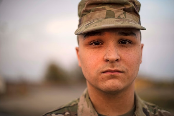 A man in a military uniform stares at the camera.
