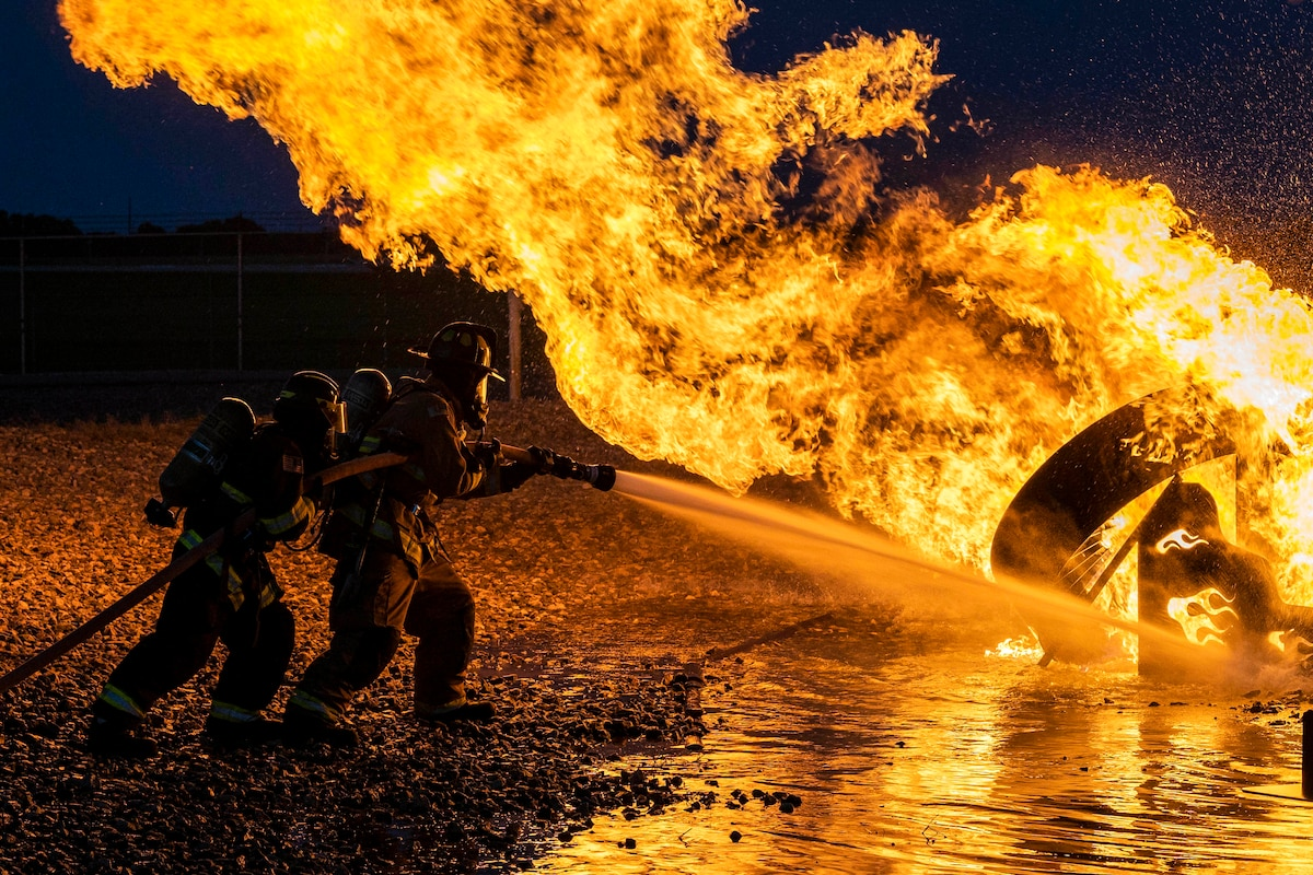 Two firefighters train a water hose on a large fire lighting up a dark blue night sky.