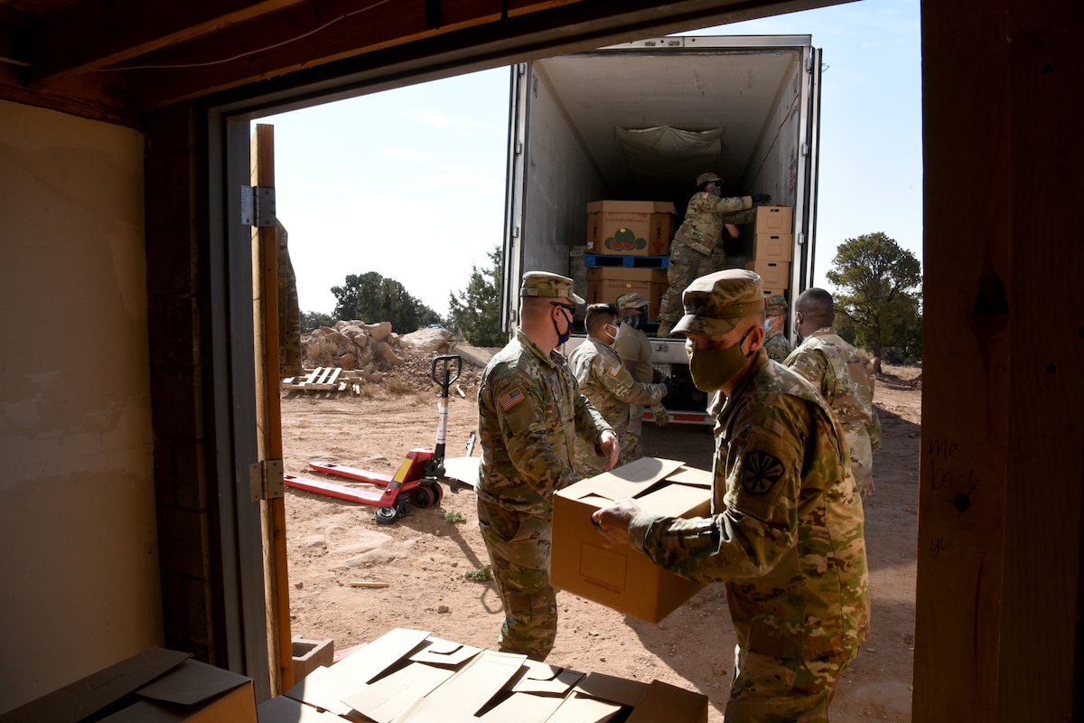 A group of male national guardsmen wearing face masks unload boxes from a truck.