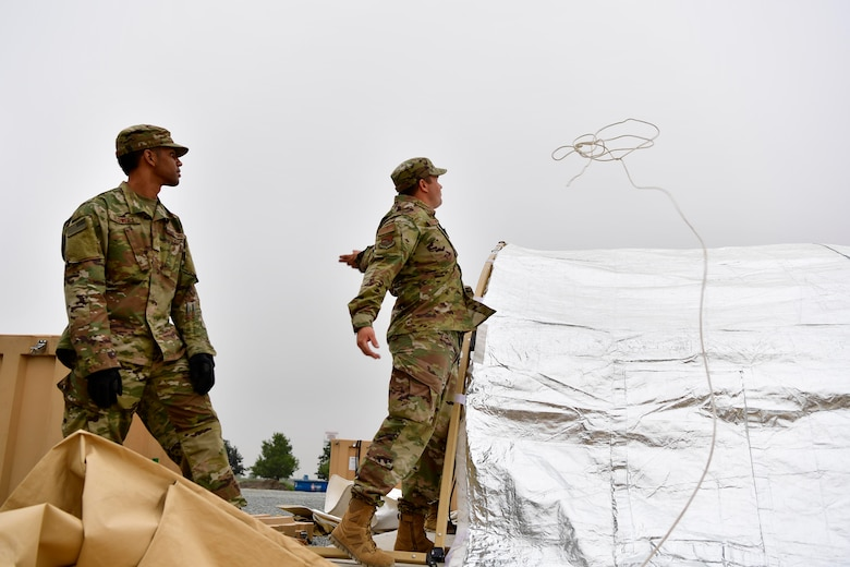 Master Sgt Dusting Fullerton, 434th Civil Engineer Squadron heavy repair superintendent throws a rope over a tent to pull the cover over on Grissom Air Reserve Base, September 10, 2020. Airmen from the 434th Civil Engineer Squadron recently put their training to the test, setting up a bare base with 24 tents, in roughly 10 hours.