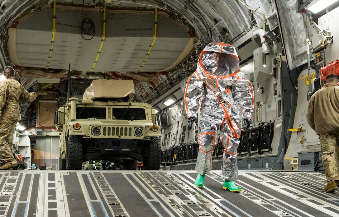 U.S. Army Maj. Mark Quint, 20th Chemical, Biological, Radiological, Nuclear and Explosives Command nuclear disablement team deputy chief, walks down the ramp of a C-17 Globemaster III, wearing personal protective equipment Sept. 19, 2020, at Dover Air Force Base, Delaware. The 20th CBRNE Command recently conducted a deployment readiness exercise, which consisted of several inspections, aerial troop movements and convoys. The 20th CBRNE Command ensures the effective countering of CBRNE hazards at home and abroad. Dover AFB serves as the primary port of embark for the 20th CBRNE Command during both exercises and operations and regularly supports similar joint missions. (U.S. Air Force photo by Roland Balik)