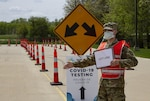 An Army PFC wearing a uniform, reflective vest and mask directs traffic with his arm extended in front of a directional sign for COVID-19 testing site.