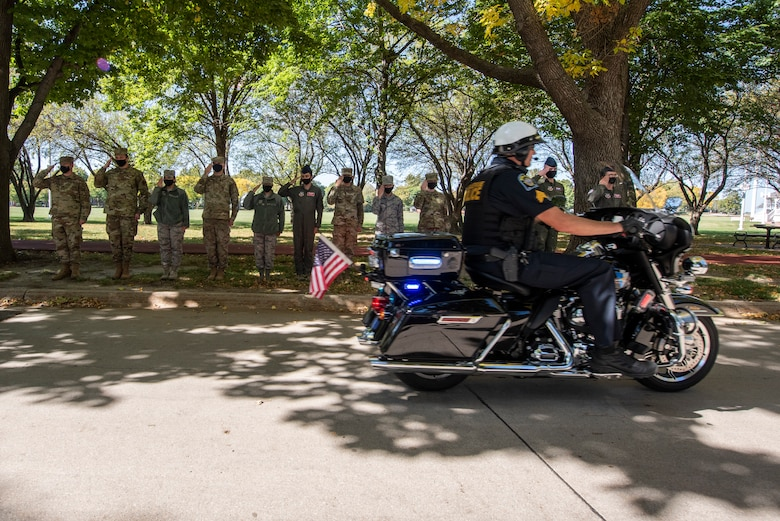 A motorcycle passes a saluting group of Airmen.