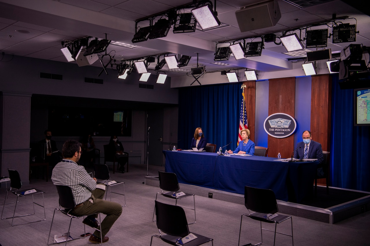 A woman, seated at a table, speaks into a microphone. The sign behind her indicates that she is at the Pentagon.