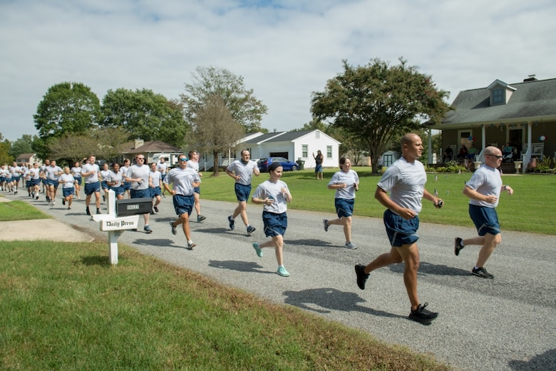 Airmen run in formation past homes in a neighborhood
